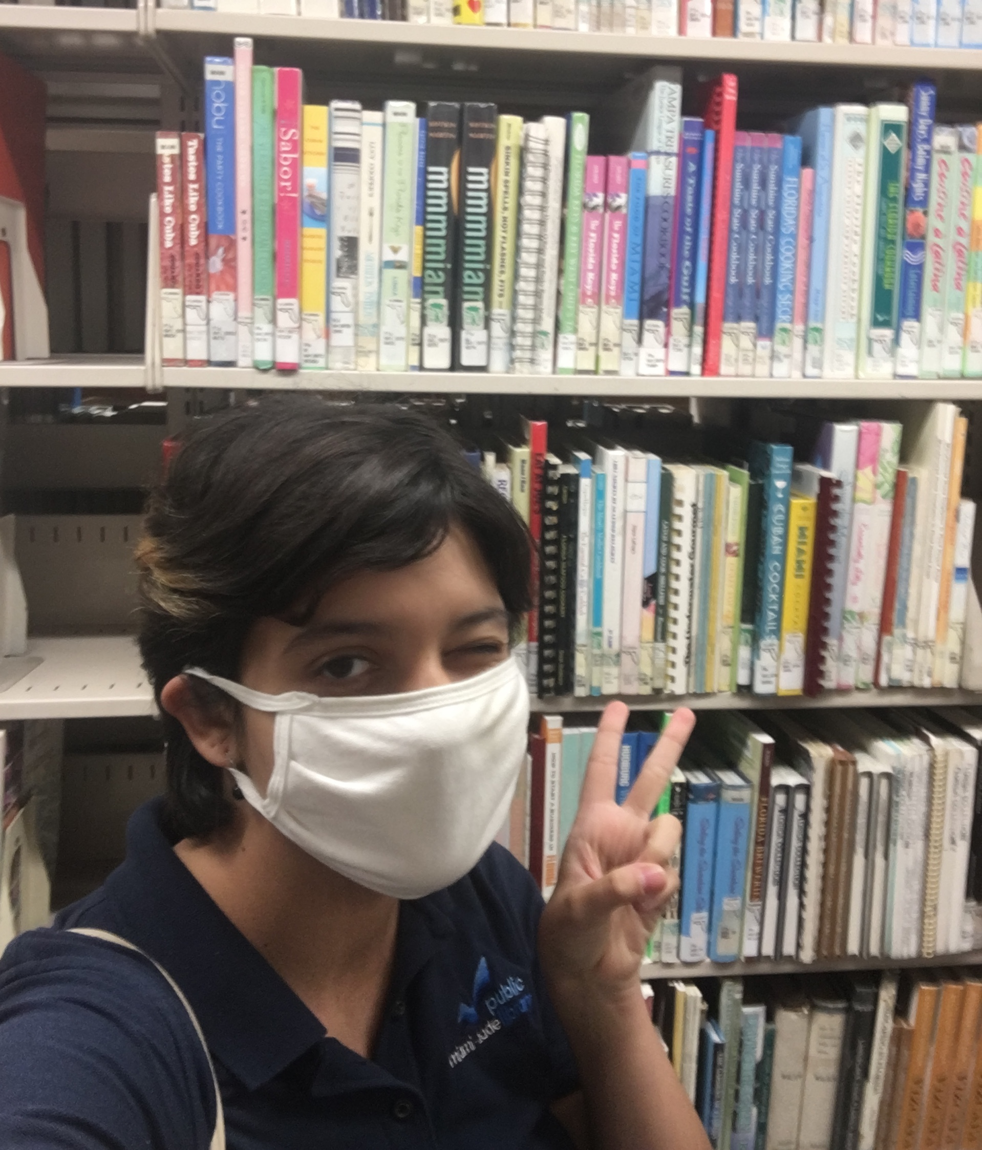 photo of person in a white mask in front of a bookshelf holding hand in a peace sign and winking
