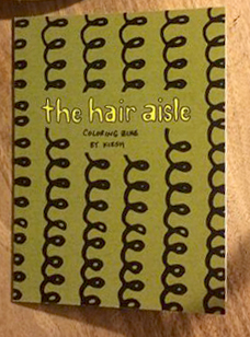 photo of The Hair Aisle Coloring Zine: green background with curls in vertical stripes, yellow title